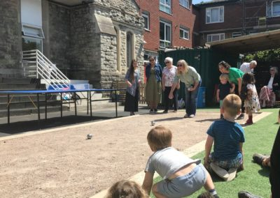 Rev. Sheridan James has a go at boules ... watched keenly by aspiring players.